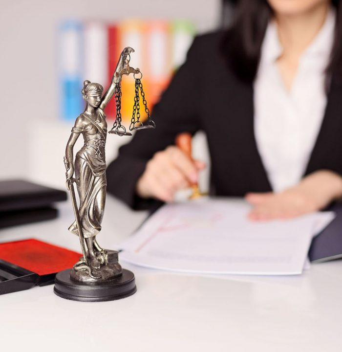 53243064 - statuette of themis - the goddess of justice on lawyer's desk. lawyer is stamping the document. law office concept.